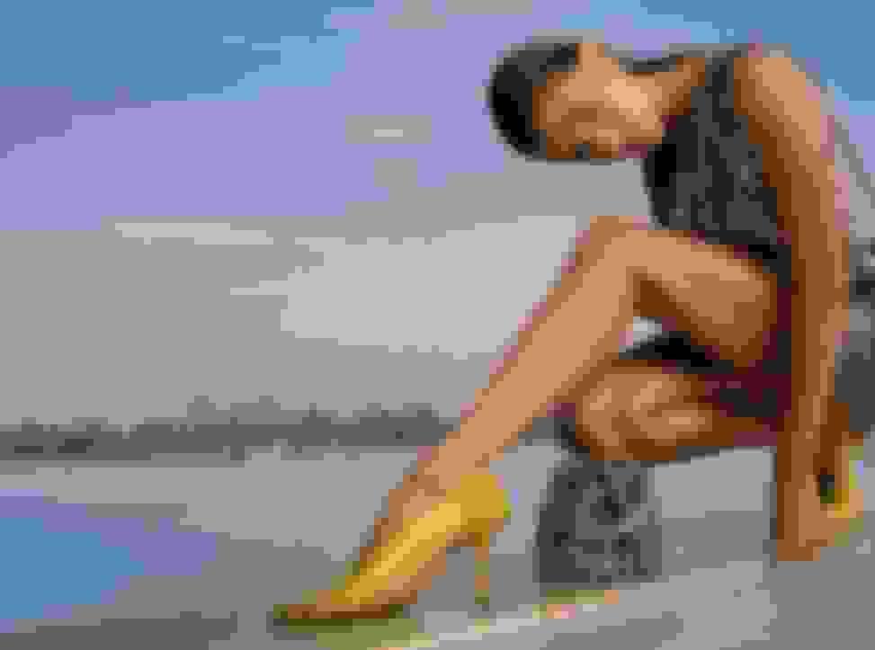 Hailey Bieber wearing Jimmy Choo women's yellow pumps and holding crystal-embellished mini handbag